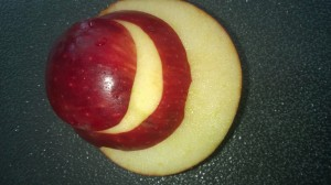 Then find your other half of the apple that we put aside earlier and using the butter knives as spacers again, cut them in to three even slices across  so that you have three rounded love heart shapes slices.